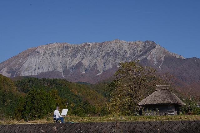 大山と藁葺小屋と画家