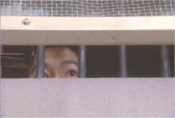 隣の受刑者と窓越しに会話を交わす南木野