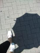 日傘の影と白いサンダル
