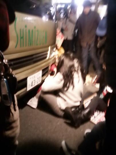 送迎バスの前に座り込む市民たち特定秘密保護法案の反対者たち=テロリスト