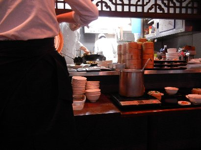 厨房と、手前でメインディッシュ以外を盛り付けする女性