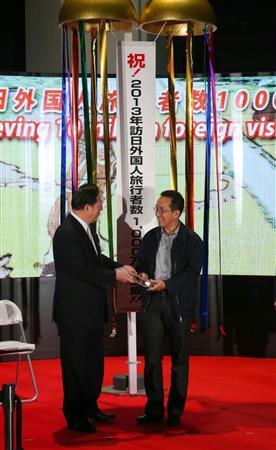 訪日外国人客が年間1000万人を突破した記念セレモニー。1000万人目のタイの事業家、パパン・パッタラプラーシットさん(右)に太田昭宏国土交通相から記念品が贈られた=20日、成田空港