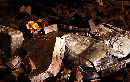 Flowers placed on the remains of a car crushed by bricks from a collapsed building on Riccarton Road, near Hagley Park.